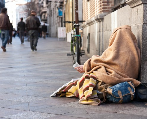 A beggar in the streets of Madrid, holding a cup for donation from passers-by.