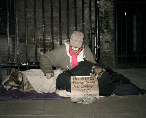 A homeless man with his two dogs begs by a walkway on the River Thames, his face shielded by his baseball cap
