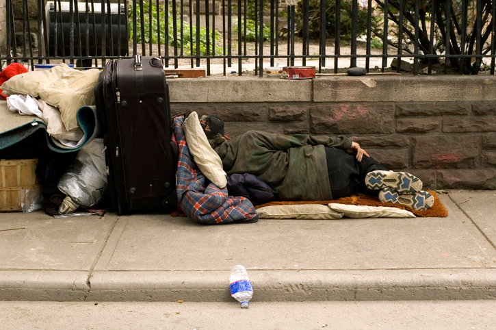Homeless person sleeping on the sidewalk with bags.