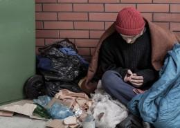 Sad homeless man sitting on the trash